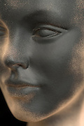 close up view of a mannequin's face with a black spray painted face