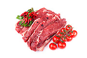 Raw beef steaks with hot chilies, parsley, cherry tomatoes and juniper grains, on white background.