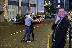 """© Licensed to London News Pictures . 17/12/2016 . Manchester , UK . A man holds his friend back in order to prevent a fight from escalating on Withy Grove . Revellers out in Manchester City Centre overnight during """" Mad Friday """" , named for being one of the busiest nights of the year for the emergency services in the UK . Photo credit : Joel Goodman/LNP"""