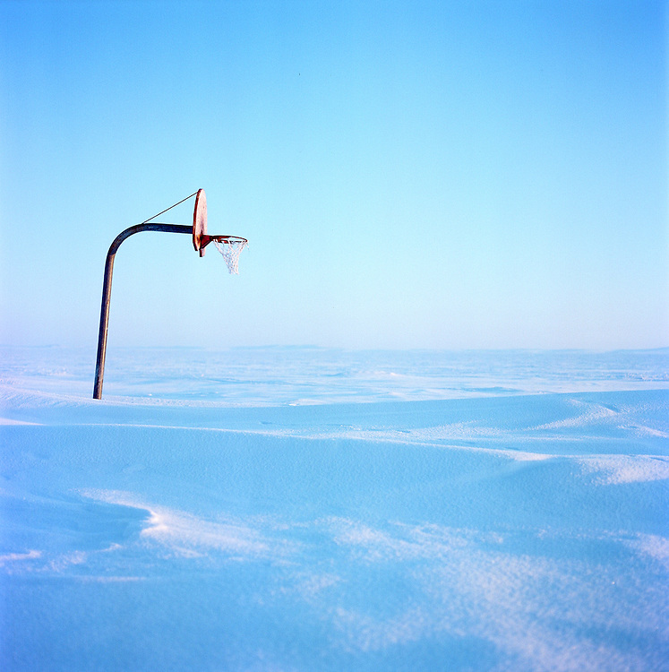 Basketball Hoop.Shishmaref, Alaska, March 2010.Shishmaref feels as though it may as well be the edge of the world. For most of the year, the Inupiat village lies muffled beneath an eclipse of snow and ice, enclosed by a frozen sea. Brightly colored homes nestle in a blue and white landscape before a seemingly endless crystalline expanse pitted against muted motions of village life. In the quiet hum of winter, the promises of distant summer stand stark and deserted-- a lone basketball hoop in a canvas of ice and snow, boats docked in wait for thawing waters.