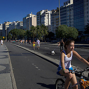 Walkers and bike riders exercise early on Sunday morning at Copacabana Beach. On Sunday's the main roads along the beaches of Copacabana, Leblon and Ipanema are closed to traffic bringing out thousands of people of all ages to walk, run, jog, ride, skateboard and cycle more than 10 km of beachside roadway. Rio de Janeiro,  Brazil. 4th July 2010. Photo Tim Clayton..