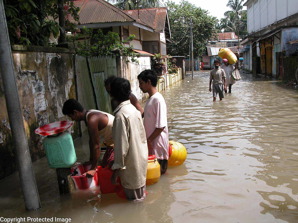Unidentified flood affected people is taking drinkingwater from a inundated pipe after the town areas inundated by floodwaters at Dhubri village, about 289 kilometers  southwest of Gauhati, capital of northeastern Indian state of Assam, Thursday, July 15, 2004. .Floodwaters of the Asia'a one of the largest river, Brahmaputra and its 35 tributaries have affected more than one million in all of Indian subcontinent and disrupted communication in many parts of the India and Bangladesh, sources said. (AP Photo/ Shib Shankar Chatterjee).