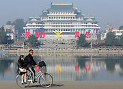 A North Korean couple ride on a bicycle as North Koreans gather at Taedong river to celebrate the 60th birthday of the North Korean ruling communist party in central Pyongyang. Photo by Lee Jae-Won (NORTH KOREA) www.leejaewonpix.com/