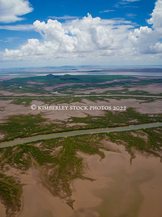 An aerial view of mangroves lining the mud flats along a  river in the wet season, east Kimberley.