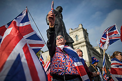 © Licensed to London News Pictures. 31/10/2019. London, UK. Pro Brexit supporters gather underneath a statue of Former British Prime minister Winston Churchill, outside the Houses of Parliament Westminster, London on October 31st, 2019, the day the UK was due to Leave the EU, before an extension was granted.. A general election will be held on December 12th.  Photo credit: Ben Cawthra/LNP