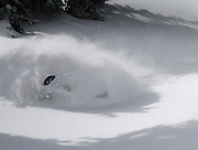 A powder wave of snow rolls over Rob Hoff and his Skidoo E tec