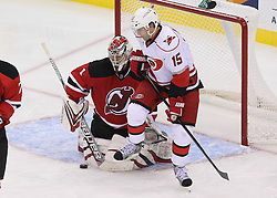 Oct 10; Newark, NJ, USA; New Jersey Devils goalie Johan Hedberg (1) makes a save while Carolina Hurricanes center Tuomo Ruutu (15) looks for the rebound during the third period at the Prudential Center. The Devils defeated the Hurricanes 4-2.