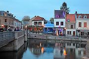 Restaurants on the Quai Belu, in the Saint-Leu area of Amiens, an area of old brick houses along a canal, restored in the 1990s, Amiens, Picardy, France. In the water is the L'Homme sur Sa Bouee or Man on his Buoy, 1993, by German artist Stephan Balkenhol, seemingly floating in the canal, one of a series of 3 oak sculptures in the Quartier Saint-Leu by the artist. Picture by Manuel Cohen