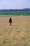 AREKJ9 Woman walking across field of freshly cut summer hay and blue sky, Burrow Hill, Suffolk, England