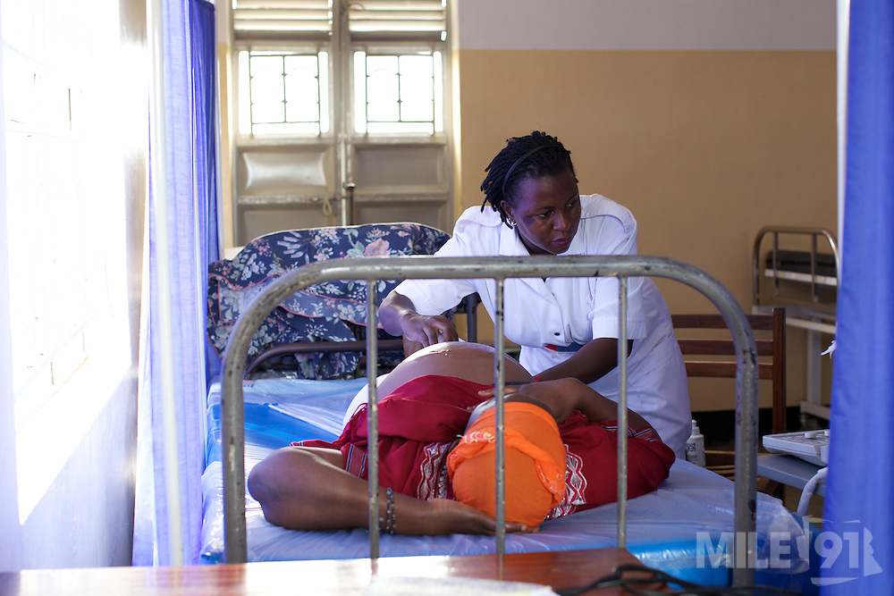 Sister Mampewo Sarah Senkungi scans a pregnant mother at Kasangati Health Centre in Uganda.