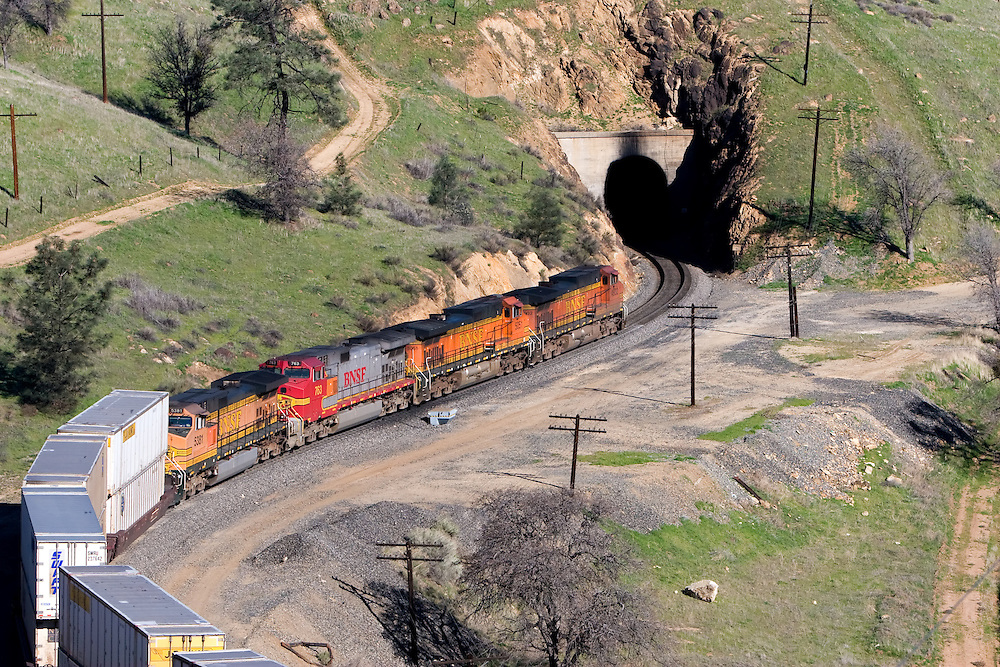 About to enter Tunnel 10 in the Tehachapi Mountains, a westbound BNSF Railway intermodal train snakes through the curves near the town of Tehachapi, CA.