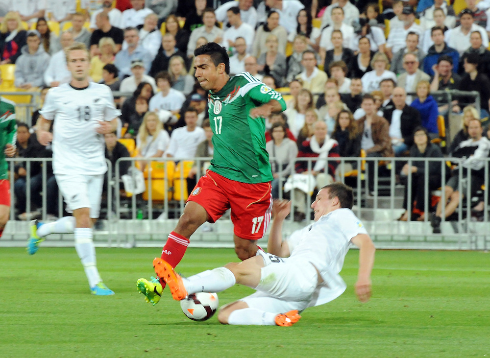 Mexico's Alonso Escoboza, left, is tackled by New Zealand's Tommy Smith in the World Cup Football qualifier, Westpac Stadium, Wellington, New Zealand, Wednesday, November 20, 2013.  Credit:SNPA / Ross Setford