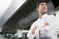 Male chef with arms crossed in kitchen low angle view