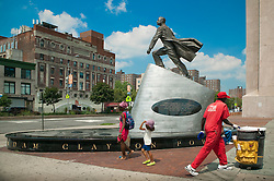 Pedestrians walk pass the bronze statue depicting Adam Clayton Powell, Jr., Press Forward, by Artist  Branly Cadet in Harlem