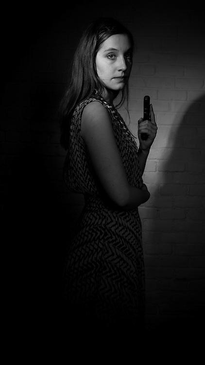 Female model holding a gun.
