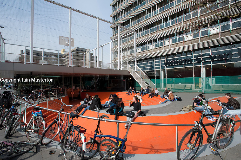 Students lounging outside The Net cafe with basketball court on roof at Utrecht University in The Netherlands