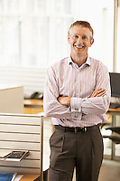 Middle-aged male office worker standing by cubicle portrait