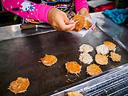 29 JUNE 2018 - BANGKOK, THAILAND: A coconut pancake vender prepares a paper tray of pancakes for a customer.       PHOTO BY JACK KURTZ