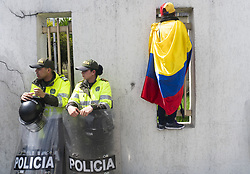 April 30, 2019 - Bogota, Colombia - A woman with the Venezuelan flag goes to the bars of the Venezuelan consulate in Bogota and two police officers are at her side. (Credit Image: © Daniel Garzon Herazo/ZUMA Wire)
