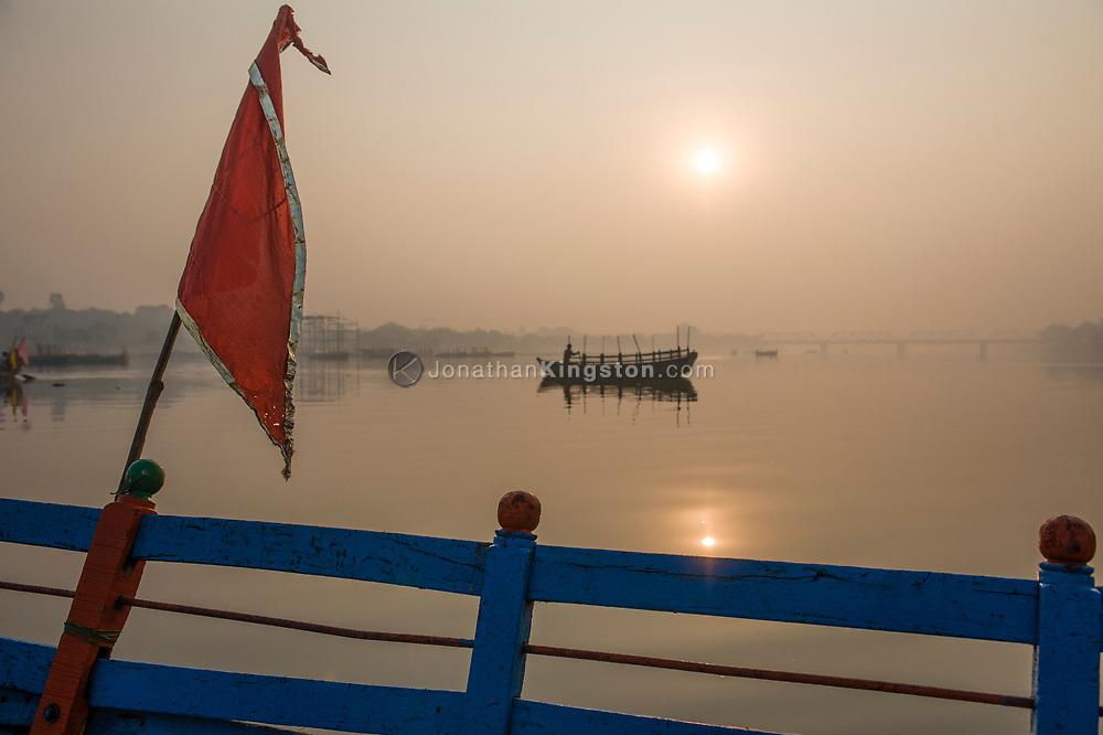 View of the Yamuna river at dawn from a boat.