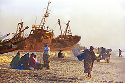 Mauritanian and Senegalese traders wait for the local fishermen to bring in the days harvest  near the capital of Nouakchott in Mauritania.  West Africa has suffered massive overfishing by foreign fishing fleets, with local small fishing boats forced to fish further and further out to sea or to concentrate their activities in sensitive coastal areas.  In the last 45 years, foreign vessels,   caught an estimated 80 percent of the fish taken from West African waters. The coastal nations took home the remaining 20 percent. And their share may get smaller..(Photo by Ami Vitale)