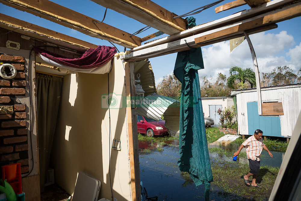 September 11, 2017 - Collier County, Florida, U.S. - ERNESTO JARA, seen from inside his family's badly damaged trailer, walks through his yard. Hurricane Irma swept through south Florida leaving behind a trail of debris, flooding and power outages.  (Credit Image: © Loren Elliott/Tampa Bay Times via ZUMA Wire)