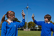 Primary school children measuring wind speeds with anemometers to help determine the best position for a second wind turbine on the school playing fields. St. Columb Minor School, Cornwall. The school won an Ashden Award in 2010 for it's appraoch to sustainable energy.