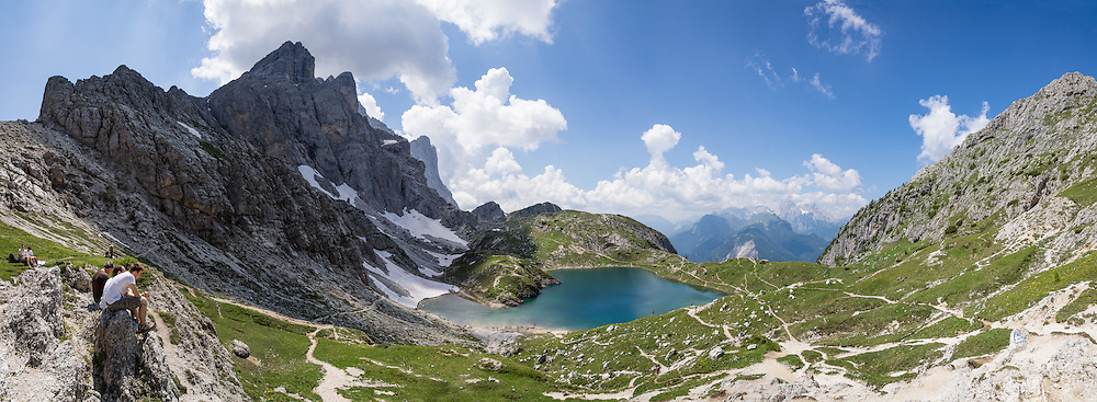 Hike to Lake Coldai on Monte Civetta, in the Dolomites, Belluno province, Veneto region, Italy, Europe. From Alleghe village, take a scenic lift to hikes on impressive Monte Civetta (3220 meters or 10,564 feet elevation). 200 million years ago, Triassic coral reefs fossilized into Dolomite. Collision of tectonic plates lifted the Dolomites within the Southern Limestone Alps. UNESCO honored the Dolomites as a natural World Heritage Site in 2009. This panorama was stitched from 8 overlapping photos.