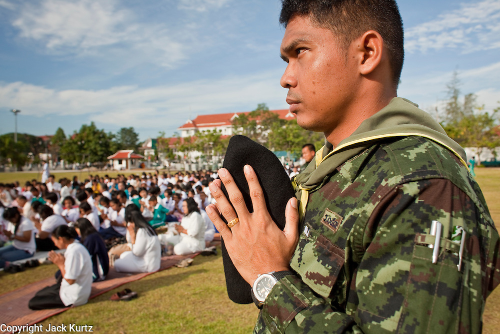 """Sept. 26, 2009 -- PATTANI, THAILAND:  A Thai soldier prays during the Tak Bat Sankatan ceremony in Pattani, Thailand Saturday. Buddhists in Thailand's three southern most provinces gathered in Pattani Saturday, Sept 26 to celebrate Tak Bat Sankatan, the day Lord Buddha returned to earth and was greeted by a crawd of his disciples and Buddhist believers who were waiting to offer him food. Buddhists monks representing the 266 """"Wats"""" (temples) in the three provinces (Pattani, Narathiwat and Yala) processed through the crowd and were presented with food and gifts.   Photo by Jack Kurtz"""