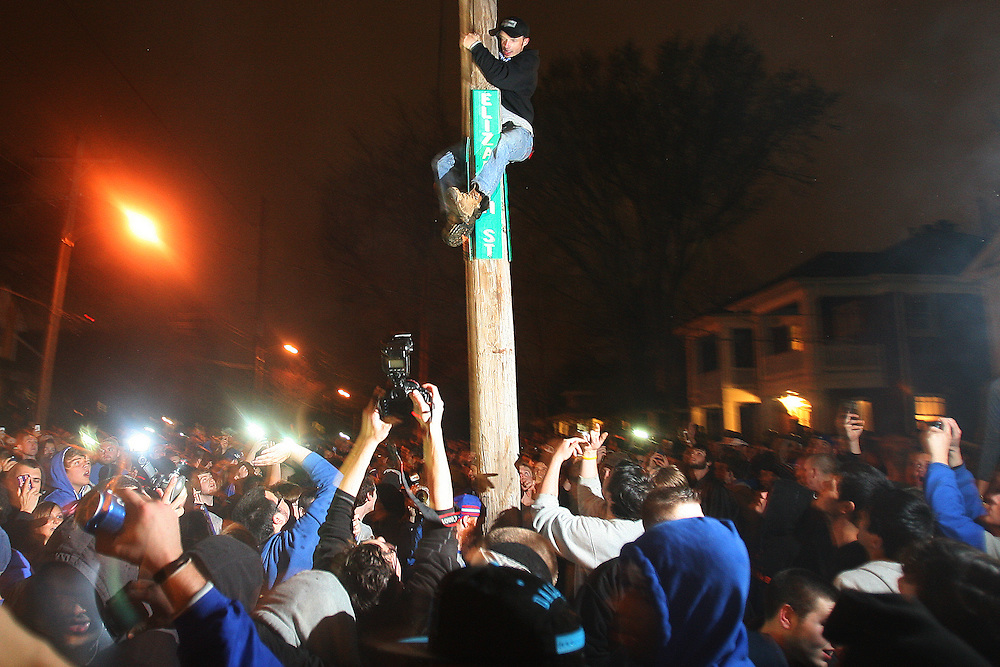 A University of Kentucky fan climbs a telephone pole at the intersection of State St. and Elizabeth St.