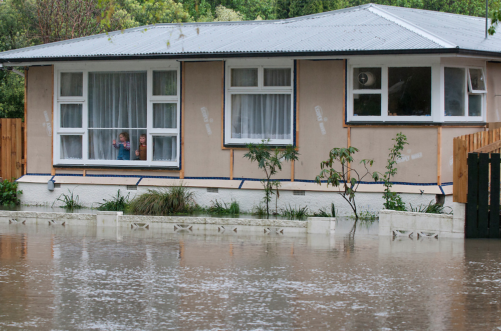 Children marooned in their home by flooding from the Heathcote River in Eastern Terrace, Christchurch, New Zealand, Wednesday, October 19, 2011. Credit: SNPA /  David Alexander.