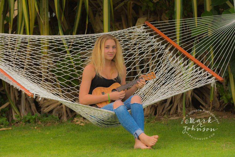 14 year old teenage girl playing the ukulele sitting on a hammock