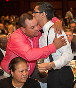 Former EMERGE student and Stanford freshman Felipe Guillen is hugged by his father during the State of the Schools luncheon, February 11, 2015.