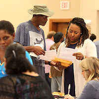 Rodney Hutton, of Tupelo, presents his paper work to Marika Baliko, Housing Coordinator with Muteh, during a Job Fair for the Homeless Thursday morning at All Saints Episcopal Church in Tupelo. Huton is working to get into an apartment with the help of Muteh.