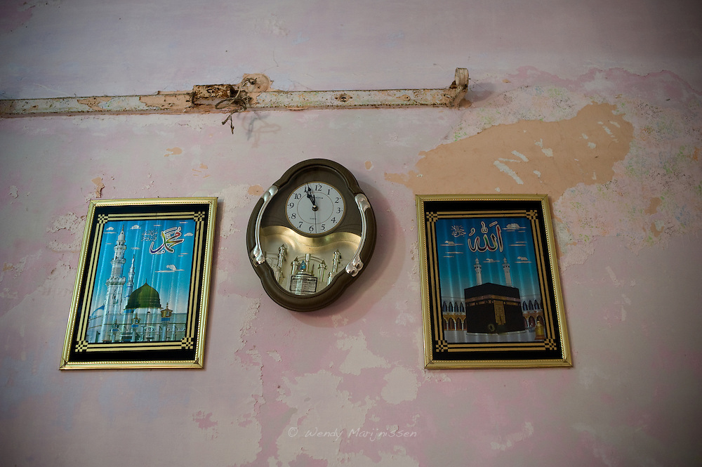 Two pictures of Mekka hang on the wall in the living room where Fatima assists women deliver their babies. Fatima Kaniz, became a dai after her husband died.  Karachi, Pakistan, 2011