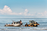 Fishing boats are towed by a tractor tug that will carry them back to land on the beach at Anchor Point, Alaska. The unique boat launch uses logging skidders to tow fishing boats from the Cook Inlet up the steep beach to the parking area and is the result of extreme tide that would make launching a boat impossible otherwise.