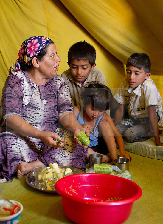 © Licensed to London News Pictures. 12/05/2013. Dohuk, Iraq. Hadia Oso Dawed (40), a Syrian refugee, prepares lunch for her family inside her tent at a refugee camp in Iraqi-Kurdistan, set up for Syrians escaping the ongoing civil war. The camp, close to the city of Dohuk, now houses in the region of 45,000 refugees, with around 400 new arrivals every day. Photo credit: Matt Cetti-Roberts/LNP