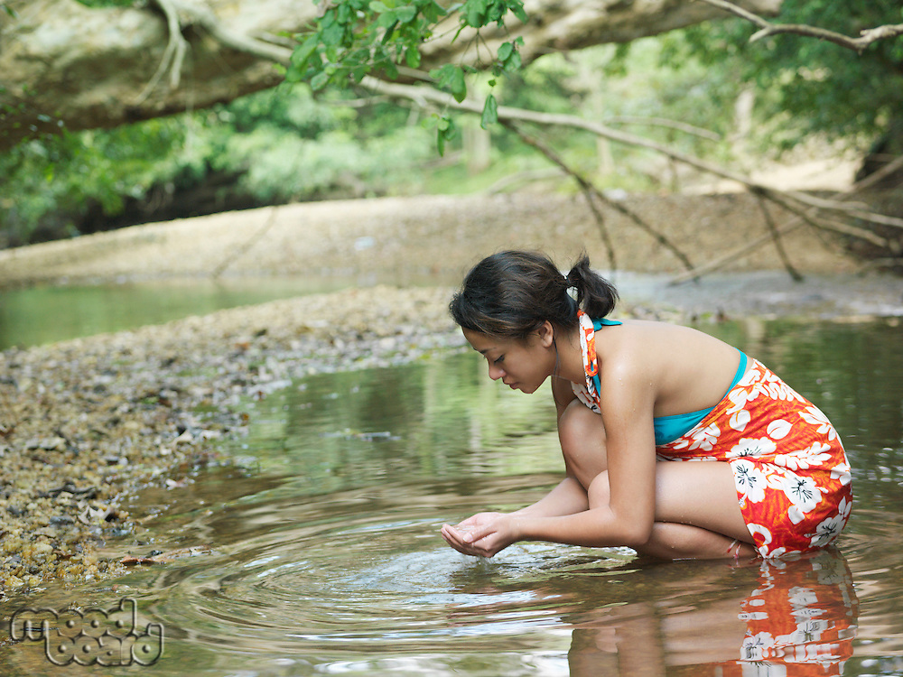 Young woman squatting in lake side view