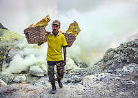 Sulfur miner, Ijen Volcano, Java, Indonesia. The Ijen miners haul on average about 80 kilograms of sulfur on their shoulders from the bottom of the volcano's crater several times every day. It is grueling and dangerous work.