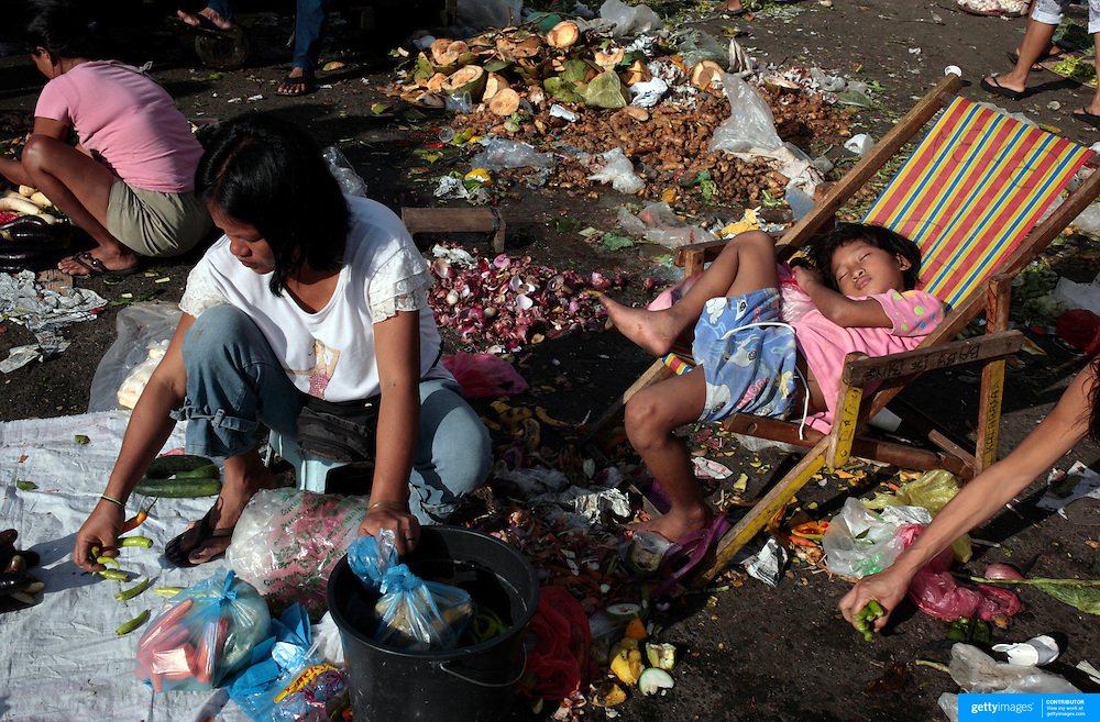 A young girl sleeps as the sunrises in an early morning scene on October 9, 2008 at Divasoria markets, Manila, the Philippines. Photo Tim Clayton