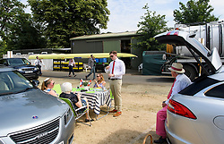 © Licensed to London News Pictures. 04/07/2018. Henley-on-Thames, UK. Rowers form Oxford University Lightweight Rowing Club carry their boat through the car park as people lunch on Day one of the Henley Royal Regatta, set on the River Thames by the town of Henley-on-Thames in England. Established in 1839, the five day international rowing event, raced over a course of 2,112 meters (1 mile 550 yards), is considered an important part of the English social season. Photo credit: Ben Cawthra/LNP