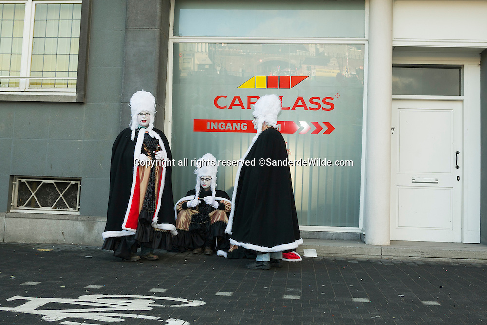 Performers dressed as women taking a break in the street in front of Carglass.Belgium, Aalst, 19th of February 2012