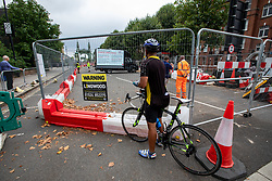 © Licensed to London News Pictures. 14/08/2020. London, UK. A cyclist stops at Hammersmith Bridge which crosses the River Thames in West London after Fulham Council suddenly closed it to all traffic Thursday night due to safety concerns. Hammersmith Bridge has been close to all traffic including pedestrians, cyclists and boats going under it after cracks in the bridge have become larger by the heatwave. Photo credit: Alex Lentati/LNP