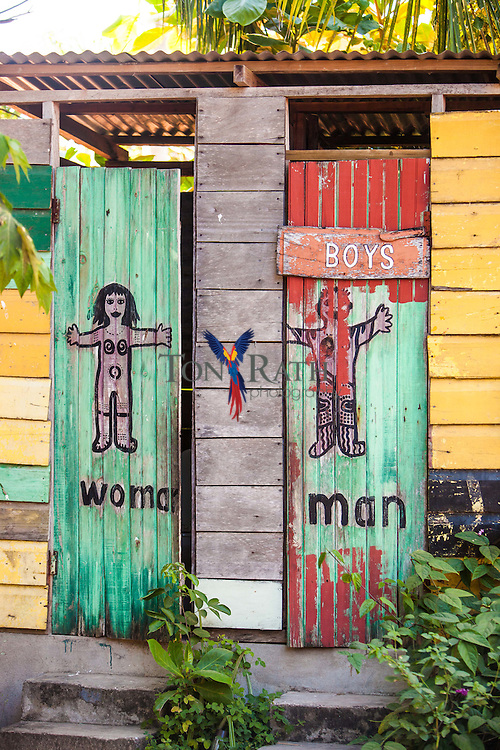 Colorfully painted signs on the doors of men's and women's outhouse doors at the Lebeha Drumming Center, Hopkins, Belize.