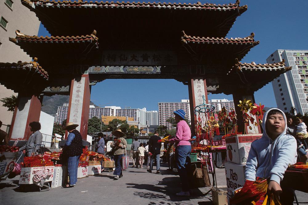 China, Hong Kong, Young boy sells souvenirs outside gates of Wong Tai Sin Temple in Kowloon Peninsula