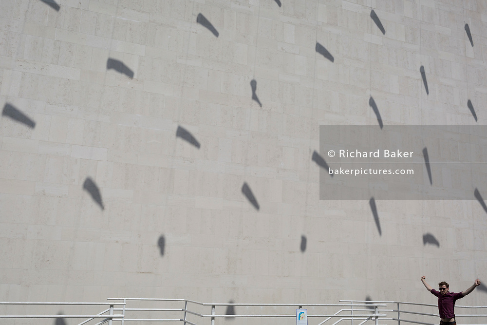 A man stretches out his arms while beneath the shadows of tube kites cast on an exterior concrete wall of the Royal Festival Hall on the Southbank, on 5th August, in London, England.