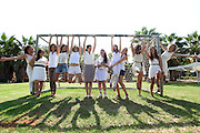 12 young women in white fooling around in a park