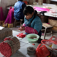 Hunan, Liuyang, Dec. 19..2013 : Cheng Yulian, a worker, assembles  fireckrackers for the Western market in a factory .