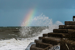 © London News Pictures. 11/01/2016. Aberystwyth, UK. A rainbow forms on the horizon as waves break against the sea wall in stormy seas, on the coastline in Aberystwyth Wales. Strong winds are affecting much of North East UK, and freezing conditions with snow are forecast for much of the country on Thursday and Friday. Photo credit:Keith Morris/LNP