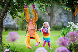 © Licensed to London News Pictures. 05/07/2019. Settle UK. 4 Year old Scarlet pushes an Orangutan made out of flowerpots on a swing at the 14th Settle Flowerpot festival in the Yorkshire Dales which takes place in the town throughout July & August. Photo credit: Andrew McCaren/LNP